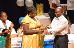 Permanent Secretary in the Premier's Ministry Wakely Daniel presents a token of appreciation to Anita Freeman of the Maude Cross Preparatory School. She was one of 10 School Ancillary staff honoured by organisers of the 2014 Warner's One Stop Family Book Feud while awardee Yule Allen of the Montessori Academy looks on