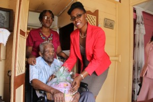 Director of the Nevis Investment Promotion Agency Kimone Moving presents a gift basket from NIPA and the Nevis Financial Services Department to Herman Ward, the oldest person in the Parish of St. Georges', at his home in Morning Star. Looking on is his daughter Hyleta Libur