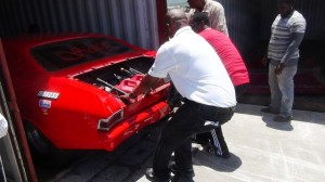 Cars being removed from containers--red car is BIG SEXY