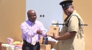L-R) Permanent Secretary in the Premier's Ministry Wakely Daniel hands over donation from the Dennis and Linda Thomas in Florida for the inmates of the Prison Farm to Principal Officer in Charge of the Prison Farm on Nevis Lawson Crosse on August 07, 2014