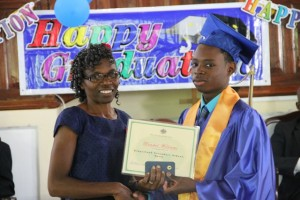 Gingerland Secondary School's 2014 Caribbean Certificate of Secondary Level Competence examinations Valedictorian Randal Williams, receives his certificate from Patron, Jennifer Liburd, at the School's 41st Graduation Ceremony at the Gingerland Methodist Church on November 27, 2014