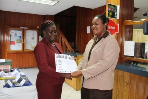 """Customer Service Manager at the Nevis Post Office Carol Jeffers (r) presents """"Officer of the Year"""" award for 2014 to Marva Morton-Parris at the Charlestown Post Office"""