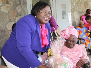 """Minister of Social development who is responsible for the welfare of the seniors on Nevis Hon. Hazel Brandy-Williams hands over a fruit basket to 103-year-old Celian """"Martin"""" Powell during her birthday celebration on January 19, 2015, at the Flamboyant Nursing Home"""