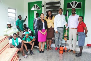 PEP Project Manager Mr Geoffrey Hanley (3rd right) and Mr Corey Tyson (2nd right) hold a weed eater during the presentation ceremony. Others in the picture are from right, Mrs Diana Pemberton, Nevis PEP staff, Ms Kerlyn Jones, and Ms Isis Morton, and members of the Gingerland Improvement Programme clean-up crew.