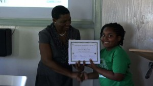 Principal Education Officer, Mrs. Palsy Wilkin, handiing over 1st Place Prize to Primary School Essay Winner, ZKaylan Williams