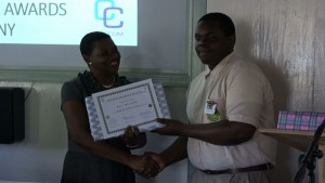 Principal Education Officer, Mrs. Palsy Wilkin, handiing over 1st Place Prize to Secondary School Essay Winner, Rol-J Williams