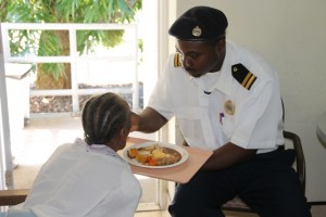 Grade II officer of the St. Kitts and Nevis Customs and Excise Department, Nevis Division Tito Huggins, feeding a resident at the Flamboyant Nursing Home on January 29, 2015