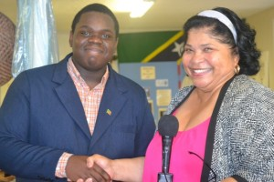 Executive Director of the Nevis Historical Conservation Society Evelyn Henville congratulates Rol-J Williams on August 05, 2015 during a send-off ceremony at the NHCS office, on his selection to represent St. Kitts and Nevis at the United States Government and World Learning 2015 Youth Ambassadors Program in Vermont, USA