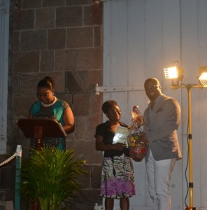 Minister of Social Development on Nevis Hon. Mark Brantley presents honouree Marjorie Brandy of the St. Georges Parish with a certificate of appreciation at the annual Charlestown Christmas Tree lighting Ceremony on December 02, 2015, for his outstanding contribution to the community