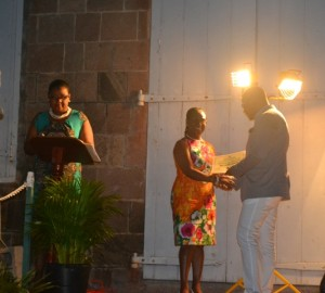 Minister of Social Development on Nevis Hon. Mark Brantley presents honouree Gloria Esdaille of the St. Paul's Parish with a certificate of appreciation at the annual Charlestown Christmas Tree lighting Ceremony on December 02, 2015, for his outstanding contribution to the community
