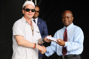 Permanent Secretary in the Premier's Ministry responsible for Education Wakely Daniel receives tickets, to attend the opening night of Nevis Blues Festival, for teachers from renowned Blues singer Ian Seigal on behalf of organisers of the festival during a presentation ceremony at Oualie Bay on April 12, 2016