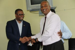 Deputy Premier of Nevis and Minister of Culture Hon. Mark Brantley hands over the cheque from Premier of Nevis Hon. Vance Amory from the Republic of China (Taiwan) to Chief Executive Officer of the Nevis Cultural Development Foundation Keith Scarborough at the Premier's office in Bath Plain on April 19, 2016